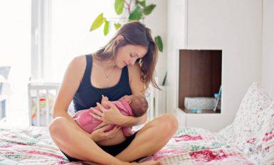 Jeune maman qui allaite son bébé assise dans son lit
